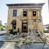 Pedestrians stop to examine a crumbling facade at the Vintner\'s Collective tasting room in Napa, Calif., following an earthquake Sunday, Aug. 24, 2014. Officials in the city of Napa say 15 to 16 buildings are no longer inhabitable after Sunday\'s magnitude-6.0 earthquake, and there is only limited access to numerous other structures. (AP Photo/Noah Berger)