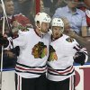 Photo - Chicago Blackhawks players Ben Smith (28) and Marcus Kruger celebrate after a goal scored against the Florida Panthers during the second period of an NHL hockey game in Sunrise, Fla., Tuesday, Oct. 22, 2013. (AP Photo/J Pat Carter)