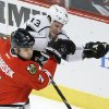 Photo - Chicago Blackhawks defenseman Brent Seabrook (7) and Los Angeles Kings left wing Kyle Clifford battle for a loose puck during the first period of an NHL hockey game Monday, Dec. 30, 2013, in Chicago. (AP Photo/Charles Rex Arbogast)