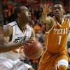 Oklahoma State\'s Markel Brown (22) looks to shoot beside Texas\' Isaiah Taylor (1) during an NCAA college basketball game between the Oklahoma State Cowboys (OSU) and the University of Texas Longhorns at Gallagher-Iba Arena in Stillwater, Okla., Wednesday, Jan. 8, 2014. Oklahoma State won 81-74. Photo by Bryan Terry, The Oklahoman