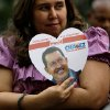 A supporter of Venezuela\'s President Hugo Chavez holds a heart-shaped placard with his image in Bolivar Square, where supporters gathered to celebrate his return, in Caracas, Venezuela, Monday, Feb. 18, 2013. Chavez returned to Venezuela early Monday after more than two months of medical treatment in Cuba following cancer surgery. Vice President Nicolas Maduro said on television that Chavez arrived at 2:30 a.m. and was taken to the Carlos Arvelo Military Hospital in Caracas, where he will continue his treatment. (AP Photo/Fernando Llano)