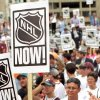 "Photo - 1996 file photo  - Downtown workers raise an ""NHL NOW!"" sign during a rally in support of a National Hockey League expansion franchise for  Oklahoma  City. Photo by Jim Beckel"