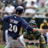 Photo - Oakland Athletics catcher Derek Norris, right, drops the ball as Milwaukee Brewers' Jonathan Lucroy slides safely into home during the third inning of a spring training baseball game on Thursday, Feb. 27, 2014, in Scottsdale, Ariz. (AP Photo/Gregory Bull)