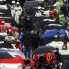 Photo - Crew members cover the cars during a weather delay at the NASCAR Sprint Cup Series auto race at Bristol Motor Speedway, Sunday, March 16, 2014, in Bristol, Tenn. (AP Photo/Wade Payne)