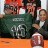 Douglass High School\'s Destin Stewart signs holds up a University of Hawaii jersey with his mother Sabena Watts looks on in Oklahoma City, Oklahoma February 4, 2009. BY STEVE GOOCH, THE OKLAHOMAN. ORG XMIT: KOD