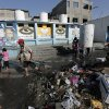 """Photo - A U.N worker cleans the garbage at the courtyard of  the Abu Hussein U.N. school, in Jebaliya refugee camp, northern Gaza Strip, Wednesday, July 30, 2014. The U.N. condemned the attack at the school on Wednesday, with Secretary-General Ban Ki Moon calling it """"outrageous"""" and """"unjustifiable."""" Israel said no U.N. facility had been intentionally targeted, but troops had responded to Hamas mortar fire nearby.  (AP Photo/Lefteris Pitarakis)"""