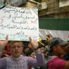 """Photo - This citizen journalism image provided by Aleppo Media Center AMC which has been authenticated based on its contents and other AP reporting, shows an anti-Syrian regime protester holds up and Arabic placard that reads: """"if you destroy my mosque I'll pray at the church, one one one the Syrian people is one, freedom, dignity,"""" during a demonstration, in Aleppo, Syria, Friday April 19, 2013. Gunmen killed a government official in a Damascus restaurant, Syrian state media and activists reported Friday as regime troops and rebels fought fierce battles near the Lebanese border.(AP Photo/Aleppo Media Center, AMC)"""