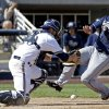Milwaukee Brewers catcher Jonathan Lucroy, left, cannot handle a throw as San Diego Padres\' Everth Cabrera scores from first on a single by Alexi Amarista during the second inning an exhibition spring training baseball game on Friday, March 7, 2014, in Phoenix. (AP Photo/Morry Gash)