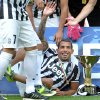 Photo - Juventus' Carlos Tevez, of Argentina, celebrates next to the Serie A trophy following the match between Juventus and Cagliari at the Juventus  Stadium in Turin, Italy, Sunday, May 18, 2014. Juventus celebrated its third straight Serie A title with a 3-0 home victory over Cagliari to set a new European record of 102 points. Antonio Conte's side had already broken the Serie A points record but ensured it moved into triple figures by also becoming the first Italian side to maintain a 100% home record. (AP Photo/Massimo Pinca)