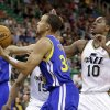 Photo - Golden State Warriors' Stephen Curry (30) drives to the basket as Utah Jazz's Alec Burks (10) defends in the first quarter during an NBA basketball game Monday, Nov. 18, 2013, in Salt Lake City. (AP Photo/Rick Bowmer)
