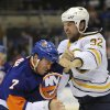 Photo - New York Islanders' Matt Carkner (7) fights with Buffalo Sabres' John Scott (32) in the first period of an NHL hockey game on Saturday, March 15, 2014, in Uniondale, N.Y. (AP Photo/Kathy Kmonicek)