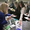In this Wednesday, Oct. 24, 2012, photo, Patricia Mazza, left, meets job seekers, including recent college grads Ashley Deyo, 22, second from left, and Chyna Dama, 23, second from right, during a National Career Fairs\' job fair, in New York. Weekly applications for U.S. unemployment benefits dropped 9,000 last week to a seasonally adjusted 363,000, the Labor Department said Thursday, Nov. 1, 2012. The level is consistent with modest hiring. (AP Photo/Bebeto Matthews)