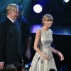 T Bone Burnett, left, and Taylor Swift, right walk to the stage to accept the award for song written for visual media for