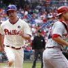 Photo - Philadelphia Phillies' Cliff Lee, left, comes in to score on a ground out by Chase Utley as Cincinnati Reds catcher Devin Mesoraco, right, looks for the ball during the fifth inning of a baseball game, Sunday, May 18, 2014, in Philadelphia. (AP Photo/Chris Szagola)