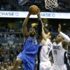 Dallas Mavericks\' Vince Carter (25) goes up for a shot around Orlando Magic\'s J.J. Redick (7) and Glen Davis (11) during the first half of an NBA basketball game, Sunday, Jan. 20, 2013, in Orlando, Fla. (AP Photo/John Raoux)
