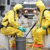 Photo - Emergency workers wearing protective suits conduct a simulated emergency exercise Thursday at the University of Central Oklahoma in Edmond. Photo by Paul Hellstern, The Oklahoman