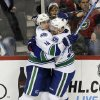 Photo - Vancouver Canucks' Alex Burrows , left, congratulates Vancouver Canucks' Daniel Sedin, of Sweden, after Sedin's goal off Minnesota Wild goalie Niklas Backstrom, of Finland, in the first period of an NHL hockey game on Thursday, Feb. 7, 2013, in St. Paul, Minn. (AP Photo/Jim Mone)