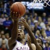 Photo - Kansas' Andrew Wiggins (22) puts up a shot under pressure from San Diego State's Dwayne Polee II during the first half of an NCAA college basketball game Sunday, Jan. 5, 2014, in Lawrence, Kan. (AP Photo/Charlie Riedel)