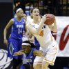 Photo - Florida Gulf Coast guard Kaneisha Atwater, left, crashes into Oklahoma State forward Liz Donohoe as they go for the ball during the second half of a first-round game in the NCAA women's college basketball tournament in West Lafayette, Ind., Saturday, March 22, 2014. Oklahoma State defeated Florida Gulf Coast 61-60 in overtime. (AP Photo/Michael Conroy)