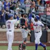 Photo - New York Mets' Chris Young (1) is greeted at home plate by Ruben Tejada (11) after hitting a two-run home run in the seventh inning of a baseball game against the Miami Marlins, Saturday, July 12, 2014, in New York. (AP Photo/Julie Jacobson)