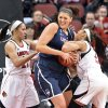 Photo - Connecticut's Stefanie Dolson, center, battles Louisville's Tia Gibbs, Left, and Bria Smith for a rebound during the first half of an NCAA college basketball game Monday, March 3, 2014, in Louisville, Ky. (AP Photo/Timothy D. Easley)
