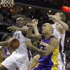 Photo - Los Angeles Lakers' Robert Sacre, center, loses the ball under the basket as the Charlotte Bobcats' Bismack Biyombo, left and Cody Zeller, right, battle during the first half of an NBA basketball game in Charlotte, N.C., Saturday, Dec. 14, 2013. (AP Photo/Bob Leverone)