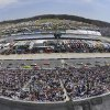 In this photo taken with a fisheye lens, the field passes the start/finish line during a warmup lap before the STP 500 NASCAR Sprint Cup series auto race at Martinsville Speedway in Martinsville, Va., Sunday April 7, 2013. (AP Photo/Don Petersen)