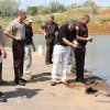 OKLAHOMA STATE BUREAU OF INVESTIGATION / MISSING BODIES FOUND: OSBI Special Agent Danny Sanders photographs a shoe discovered in Foss Lake, believed to be from one of two submerged vehicles pulled out of the lake today. Photo by Larissa Graham,The Elk City News