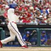 Photo - Philadelphia Phillies' Jimmy Rollins hits a single during the fifth inning of a baseball game against the Chicago Cubs, Saturday, June 14, 2014, in Philadelphia. This single gives Jimmy Rollins the all time hits leader for the Philadelphia Phillies. (AP Photo/Chris Szagola)