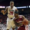 Photo - Oklahoma's Cameron Clark, right, looks to pass as Texas Tech's Toddrick Gotcher (20) defends during an NCAA college basketball game in Lubbock, Texas, Saturday, Jan. 25, 2014. (AP Photo/The Avalanche-Journal, Tori Eichberger)