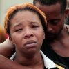 Photo - Lesley McSpadden, left, is comforted by her husband, Louis Head, after her 18-year-old son, Michael Brown was shot and killed by police in the middle of the street in Ferguson, Mo., near St. Louis on Saturday, Aug. 9, 2014. A spokesman with the St. Louis County Police Department, which is investigating the shooting at the request of the local department, confirmed a Ferguson police officer shot the man. The spokesman didn't give the reason for the shooting. (AP Photo/St. Louis Post-Dispatch, Huy Mach)