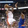 Photo - Toronto Raptors' Kyle Lowry, left, shoots against New York Knicks' Toure' Murry during first-half NBA basketball game action in Toronto, Saturday, Dec. 28, 2013. (AP Photo/The Canadian Press, Chris Young)