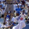Los Angeles Dodgers\' Yasiel Puig, right, scores on a single by Adrian Gonzalez as Colorado Rockies catcher Wilin Rosario takes a high throw during the fifth inning of a baseball game, Sunday, July 14, 2013, in Los Angeles. (AP Photo/Mark J. Terrill)