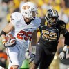 Oklahoma State\'s Josh Cooper (25) carries the ball as Missouri\'s Michael Sam (52) pursues in the first quarter during a college football game between the Oklahoma State University Cowboys (OSU) and the University of Missouri Tigers (Mizzou) at Faurot Field in Columbia, Mo., Saturday, Oct. 22, 2011. Photo by Nate Billings, The Oklahoman