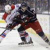 Photo - Washington Capitals' Troy Brouwer, left, and Columbus Blue Jackets' Cody Goloubef fight for a loose puck during the first period of an NHL hockey game, Thursday, Jan. 30, 2014, in Columbus, Ohio. (AP Photo/Jay LaPrete)