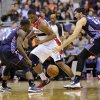 Photo - Charlotte Bobcats' Ben Gordon, left, and Byron Mullens (22) look for the loose ball against Washington Wizards forward Kevin Seraphin, center, during the first half of an NBA basketball game, Saturday, March 9, 2013, in Washington. (AP Photo/Nick Wass)