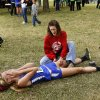 Tristan Wood, a sophomore member of the Holdenville High School cross country team, lays beneath a tree after finishing the course in the Class 3A Girls cross country championship event in Shawnee on Saturday, Oct. 26, 2013. Her mother, Kim, is massaging her daughter\'s thigh to give Tristan some relief from agonizing pain. Tristan\'s parents said she has been battling a torn muscle in her thigh for most of this season. Photo by Jim Beckel, The Oklahoman.