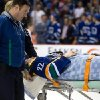 Vancouver Canucks\' Daniel Sedin, of Sweden, is taken off the ice on a stretcher after being checked into the boards by Calgary Flames\' Paul Byron during second period NHL hockey action in Vancouver, British Columbia, on Sunday April 13, 2014. (AP Photo/The Canadian Press, Darryl Dyck)