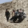 Afghans push parts of a damaged vehicle off a hill after a roadside explosion on the outskirts of Laghman province east of Kabul, Afghanistan, Sunday, Aug. 12, 2012. A provincial spokesman says a roadside bomb has killed a district chief in eastern Afghanistan and three of his bodyguards. (AP Photo/Rahmat Gul)