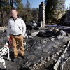 Rick Heltebrake with his dog Suni looks over the burned-out cabin where Christopher Dorner\'s remains were found after a police standoff Tuesday near Big Bear, Calif., Friday Feb. 15, 2013. Heltebrake had been carjacked by Dorner. (AP Photo/Nick Ut)