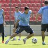 Photo - Martin Carceres and Jorge Fucili, back, observes Luis Suarez, center, dribble at a practice session at Arena do Jacare Stadium, for the Brazil 2014 World Cup in Sete Lagoas, Brazil, Saturday, June 21, 2014. Uruguay plays in group D at the 2014 soccer World Cup. (AP Photo/Bruno Magalhaes)