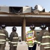 Oklahoma City firemen watch from below I-40 during the rescue of a semi truck driver who\'s trailer load of gravel flipped and came to rest hanging over the edge of the I-40 Crosstown Expressway Bridge in Oklahoma City Friday, Aug. 26, 2011. Photo by Paul B. Southerland, The Oklahoman