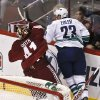 Photo - Vancouver Canucks' Alexander Edler (23), of Sweden, knocks Phoenix Coyotes' Mike Smith (41) to the ice, and gets called for a five-minue charging penalty, during the second period in an NHL hockey game, Thursday, March 21, 2013, in Glendale, Ariz. (AP Photo/Ross D. Franklin)