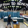 Photo - Julie Tuchscher pushes a cart loaded with sunglasses Thursday at the Cox Convention Center in preparation for the Oklahoma City Memorial Marathon.  Photos By Steve Gooch, The Oklahoman