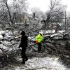 People work to clear a large tree that fell on a car traveling on East Market St in York, Pa. (AP Photo/York Daily Record, Paul Kuehnel ) YORK DISPATCH OUT