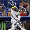 Oakland Athletics\' Josh Donaldson hits a two-out RBI single to score Brandon Moss for the go-ahead run during the 14th inning of a baseball game against the Miami Marlins, Saturday, June 28, 2014 in Miami. The Athletics won 7-6 in 14 innings. (AP Photo/Wilfredo Lee)