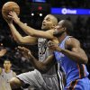 Photo - San Antonio Spurs guard Tony Parker, left, shoots against Oklahoma City Thunder forward Serge Ibaka during the first half of an NBA basketball game, Saturday, Dec. 21, 2013, in San Antonio. (AP Photo/Darren Abate)