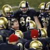 """FILE - In this Oct. 6, 2012, file photo, Notre Dame head coach Brian Kelly, center left, talks to his team during the second half of an NCAA college football game against Miami at Soldier Field in Chicago. About the only thing the Irish haven't done yet this season is rally from behind to win. The Irish have been able to ignore what coach Kelly refers to as the """"noise"""" so far, but it keeps getting louder with every victory.(AP Photo/Charles Rex Arbogast, File)"""