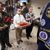 Photo - Josh Royer, 14, of Stratham, N.H., left, Alex Cardona, 11, of York, Maine, center, and Alex Coulombe, 11, of Freemont, N.H., offer roses and programs before a service marking the 50th anniversary of the sinking of the USS Thresher, Saturday, April 6, 2013, at the high school in Portsmouth, N.H. (AP Photo/Michael Dwyer)