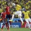 Photo - Brazil's David Luiz head the ball next to Colombia's Juan Cuadrado during the World Cup quarterfinal soccer match between Brazil and Colombia at the Arena Castelao in Fortaleza, Brazil, Friday, July 4, 2014. (AP Photo/Hassan Ammar)
